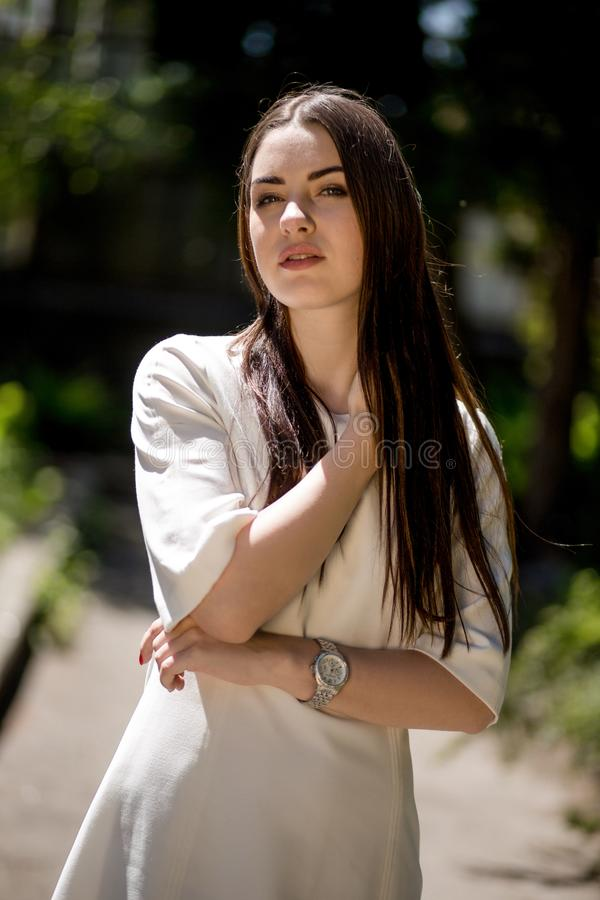 Jonge Donkerbruine Vrouw in het Park wat betreft Haar Hals met Rechts haar stock fotografie