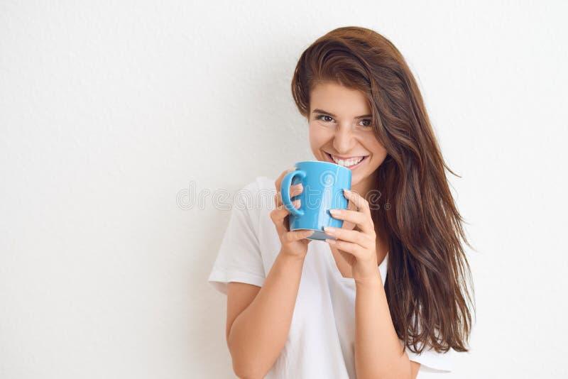 Jonge donkerbruine vrouw in het witte t-shirt drinken van blauwe mok stock afbeelding