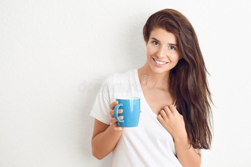 Jonge donkerbruine vrouw in het witte t-shirt drinken van blauwe mok royalty-vrije stock fotografie