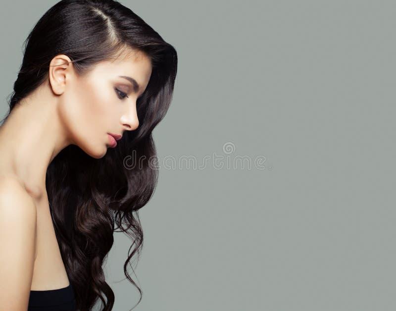 Jonge donkerbruine vrouw met lang perfect kapsel Haarverzorging en schoonheidssalonachtergrond royalty-vrije stock fotografie