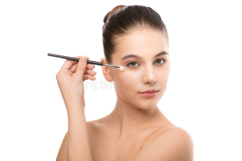 Jonge donkerbruine vrouw met schoon gezicht Meisjes perfecte huid die kosmetische borstel toepassen Geïsoleerdn op een wit royalty-vrije stock foto's