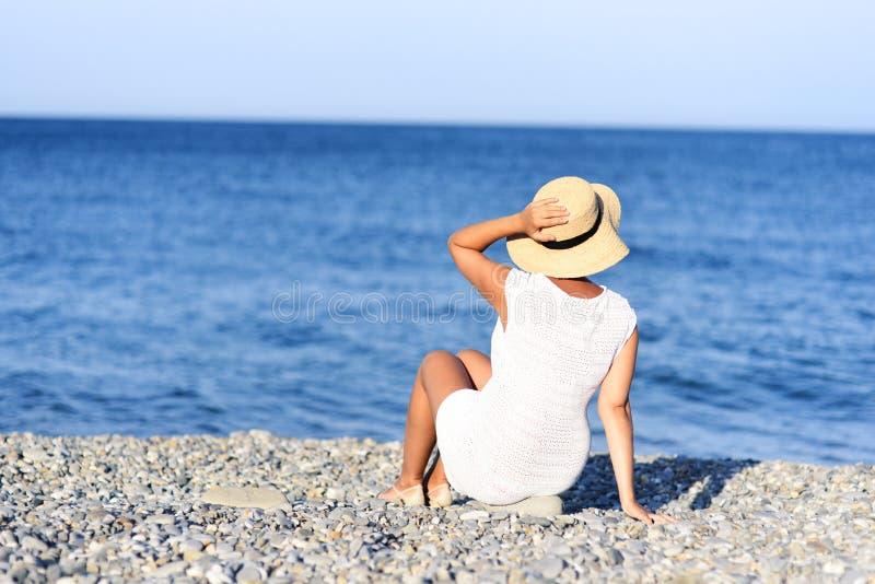 Jonge donkerbruine vrouw in plaatsing van de de zomer de witte kleding op strand en het kijken aan het overzees Kaukasisch en mei royalty-vrije stock afbeelding