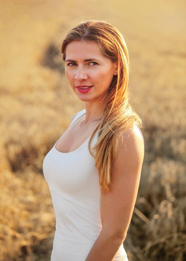 Jonge donkerbruine vrouw in witte kleding, die zich op die tarwegebied bevinden door middagzon wordt aangestoken royalty-vrije stock fotografie