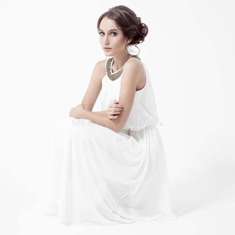 Jonge donkerbruine vrouw in witte kleding. Witte Achtergrond. royalty-vrije stock foto