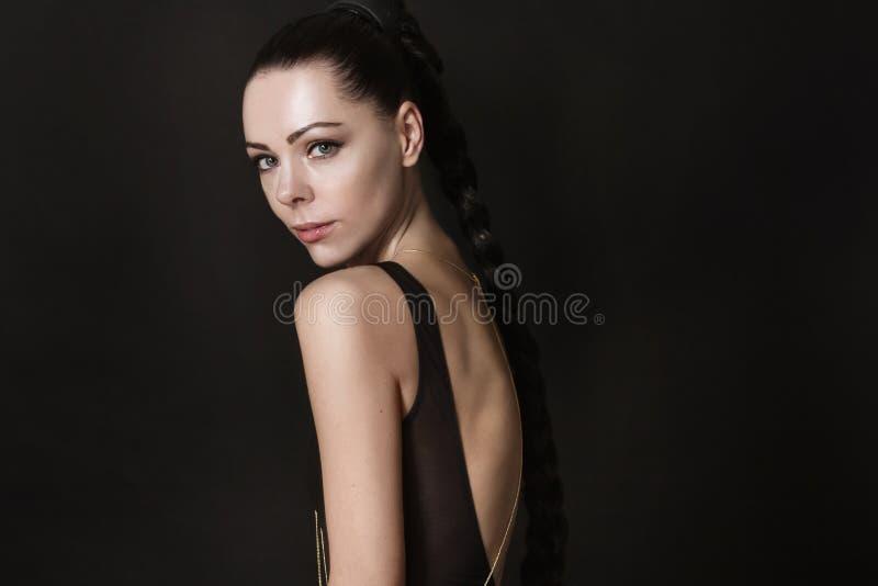 Jonge donkerbruine vrouw in zwart kledingstuk royalty-vrije stock foto's