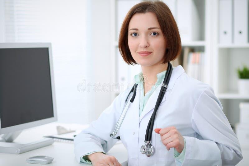 Jonge donkerbruine vrouwelijke artsenzitting bij de lijst en het werken met computer op het ziekenhuiskantoor stock foto's