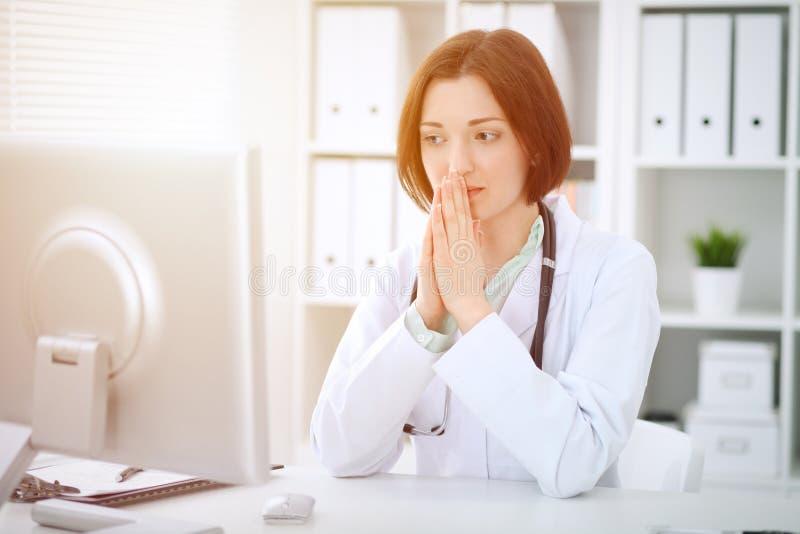Jonge donkerbruine vrouwelijke artsenzitting bij de lijst en het werken met computer op het ziekenhuiskantoor royalty-vrije stock afbeeldingen