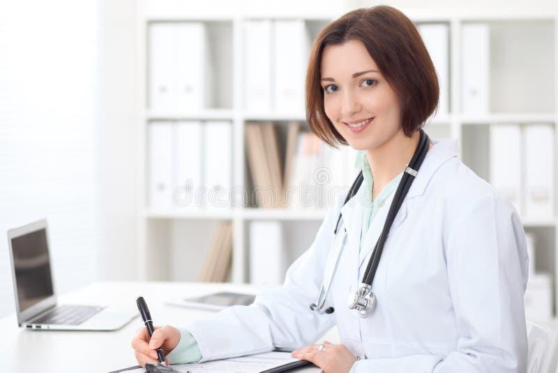 Jonge donkerbruine vrouwelijke artsenzitting bij de lijst en het werken op het ziekenhuiskantoor royalty-vrije stock fotografie