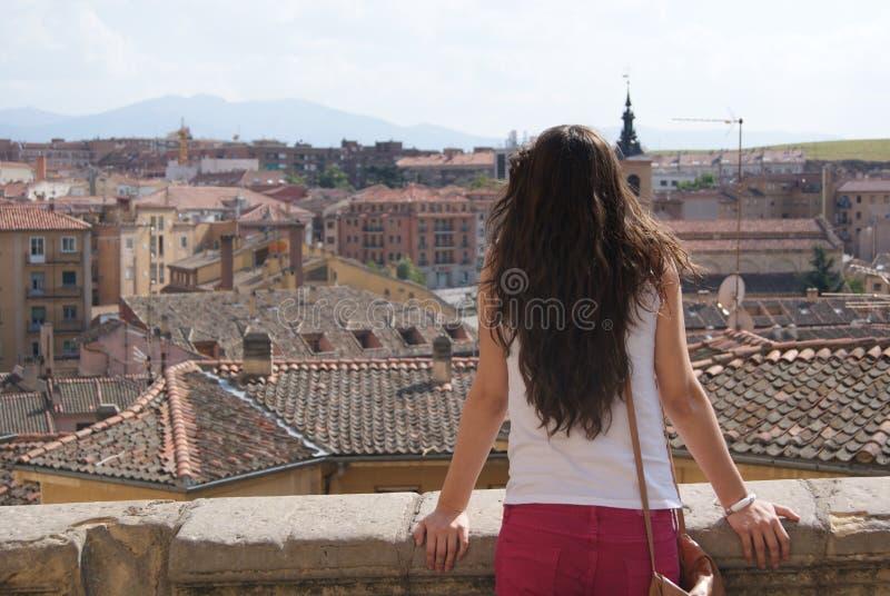 Jonge donkerbruine vrouwentoerist die de oude stadsmening bekijken over de daken stock afbeelding