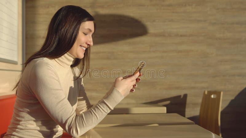 Jonge donkerbruine vrouwenzitting in koffie met telefoon Virtuele mededeling royalty-vrije stock afbeelding