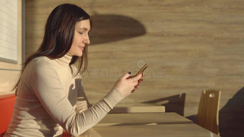 Jonge donkerbruine vrouwenzitting in koffie met telefoon Virtuele mededeling stock afbeelding