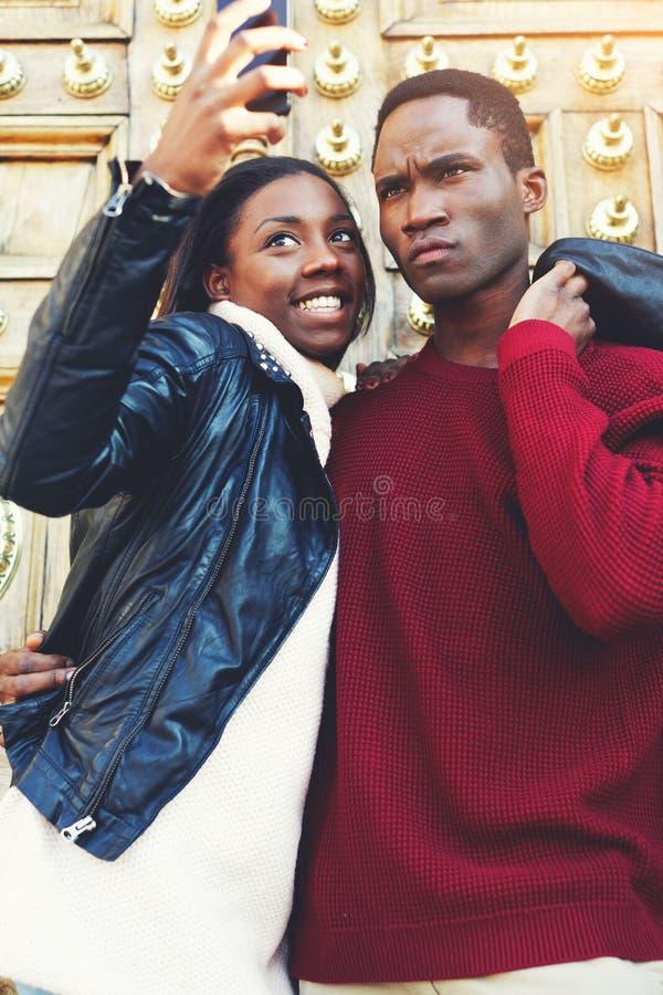 Jonge donkere gevilde man en vrouw die terwijl het fotograferen van op mobiele telefooncamera terwijl in openlucht status stellen royalty-vrije stock foto's