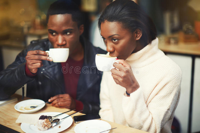 Jonge donkere gevilde man en vrouwen het drinken koffie terwijl het zitten samen in moderne koffie in koude de winterdag royalty-vrije stock afbeelding