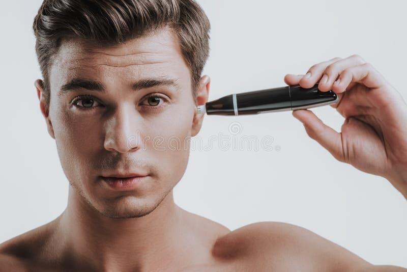 Jonge donkere haired mens die snoeischaar voor zijn oor met behulp van royalty-vrije stock afbeelding