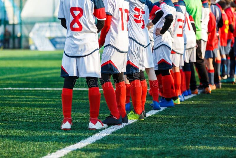 Jonge dribble van voetballersjongens, de bal van de schopvoetbal in spel Jongens in rode witte sportkleding die op voetbalgebied  stock foto's