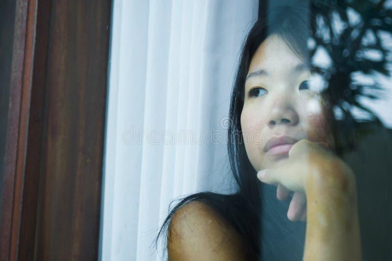 Jonge droevige en gedeprimeerde Aziatische Chinese vrouw die nadenkend door vensterglas die aan pijn en depressie in droefheidsco stock foto's