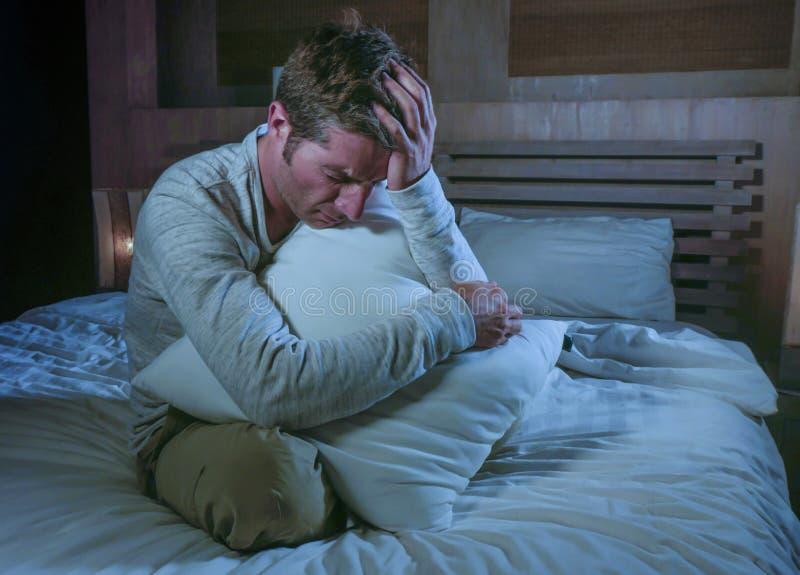 Jonge droevige en wanhopige mensen wakkere recent - nacht op bed in duisternis aan depressie lijden en bezorgdheid die beklemtoon royalty-vrije stock afbeelding