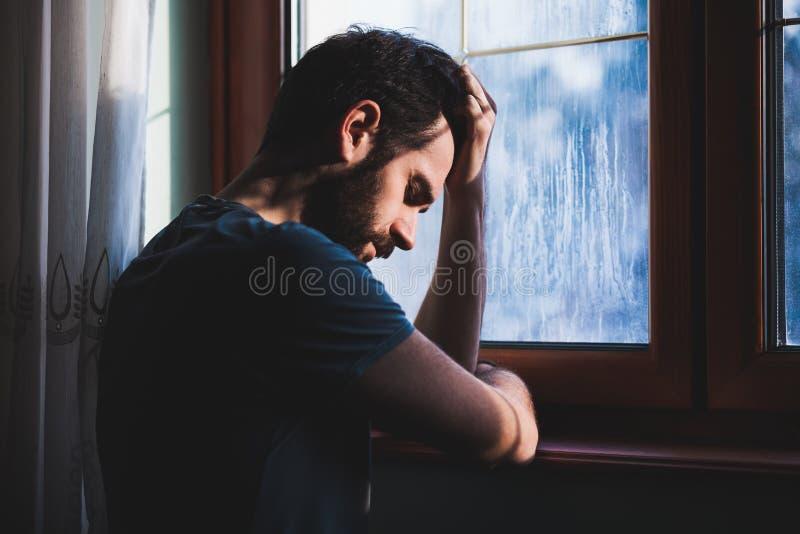 Jonge droevige gekke zitting door het venster royalty-vrije stock foto