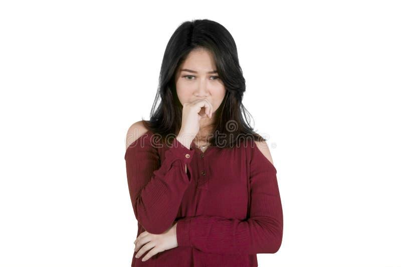 Jonge droevige vrouw die iets op studio denken stock foto's