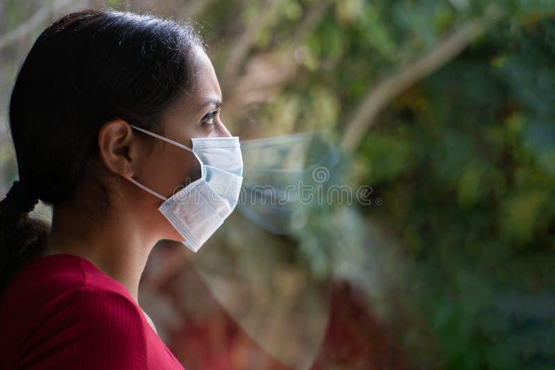 Jonge droevige vrouw met een gezichtsmasker die door het raam kijkt met haar reflectie op het glas Coronavirus en Quarentine royalty-vrije stock afbeeldingen