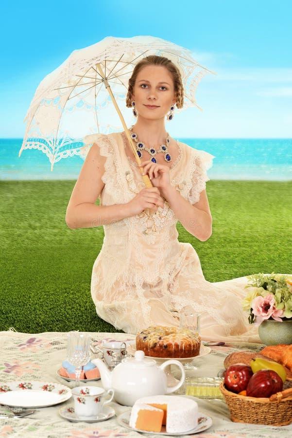 Jonge edwardian vrouw bij picknick met paraplu stock afbeeldingen