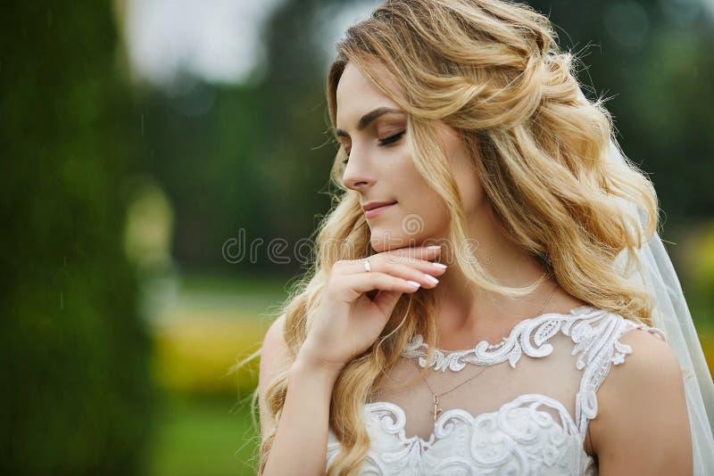 Jonge elegante blondebruid met gesloten ogen en met modieus huwelijkskapsel in kant witte kleding in openlucht royalty-vrije stock foto's