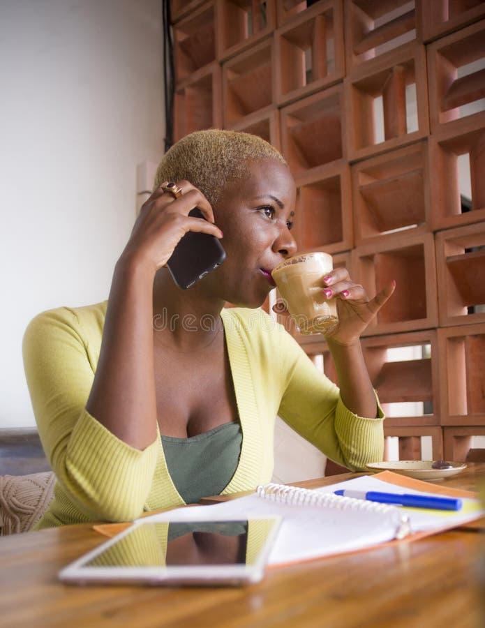 Jonge elegante en mooie zwarte Afrikaanse Amerikaanse bedrijfsvrouw die online met mobiele telefoon bij koffiewinkel het drinken  royalty-vrije stock fotografie