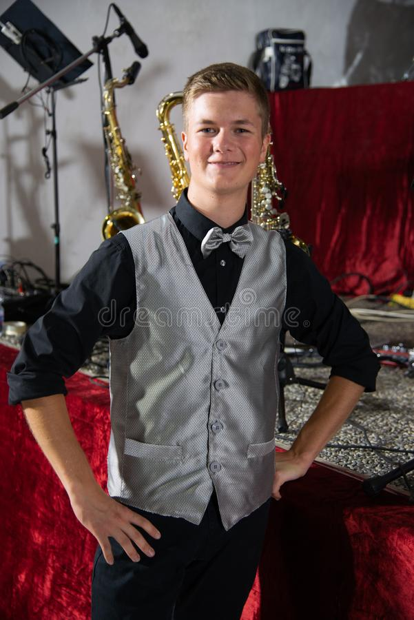 Jonge elegante jongen met zilveren-gekleurde vlinderdas, zilveren-gekleurd Vest, die vóór een muzikaal overleg glimlachen royalty-vrije stock foto's