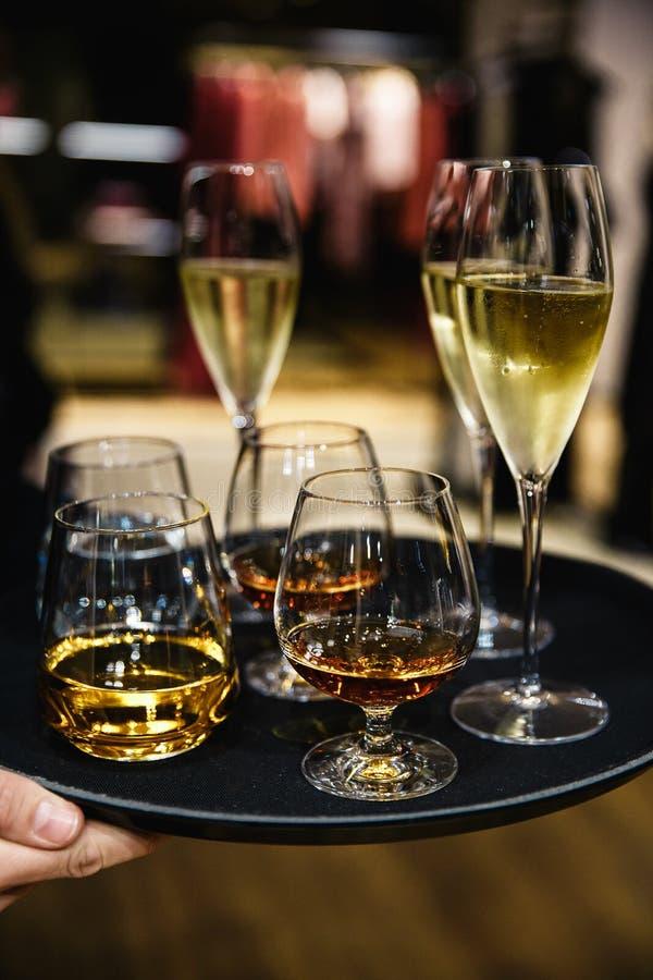 Jonge elegante mens die zich in het restaurant bevinden, die een plaat met glazen wijn en cognac, wisky houden Mensen` s stijl stock afbeelding