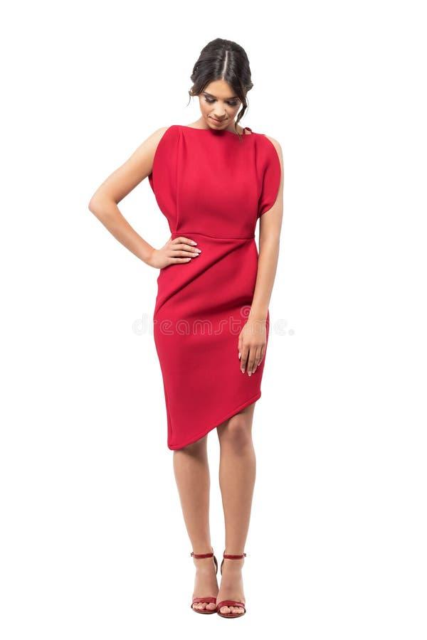 Jonge elegante modevrouw die in rode avondjurk neer kijken royalty-vrije stock foto