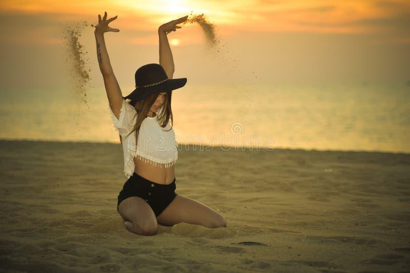 Jonge elegante mooie dame met een hoed op de achtergrond van de stranddageraad in openlucht, portret royalty-vrije stock foto