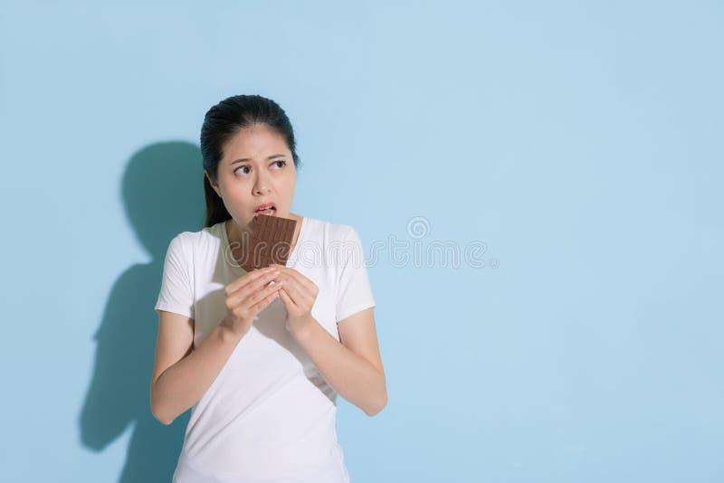 Jonge elegante vrouw die zoete chocolade eten royalty-vrije stock afbeeldingen