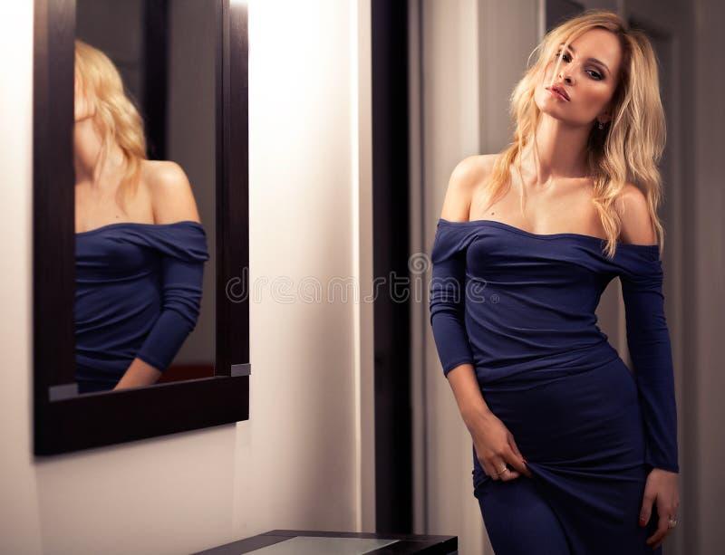 Jonge elegante vrouw in lange blauwe kleding in binnenland met spiegel royalty-vrije stock afbeelding