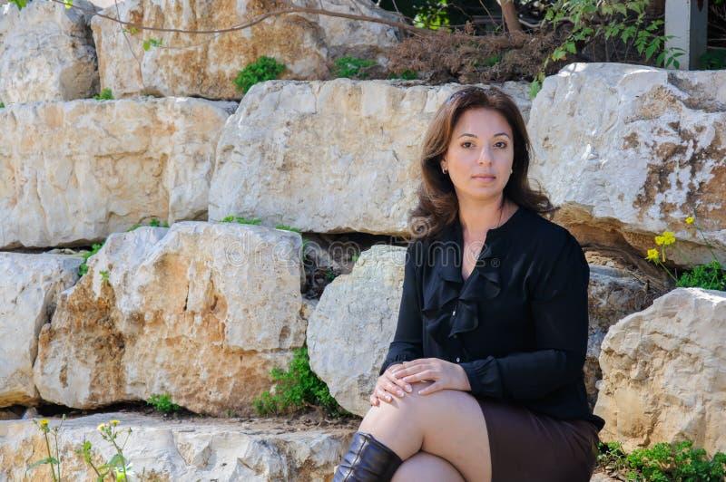 Jonge elegante vrouwenzitting buiten op stenen stock afbeeldingen