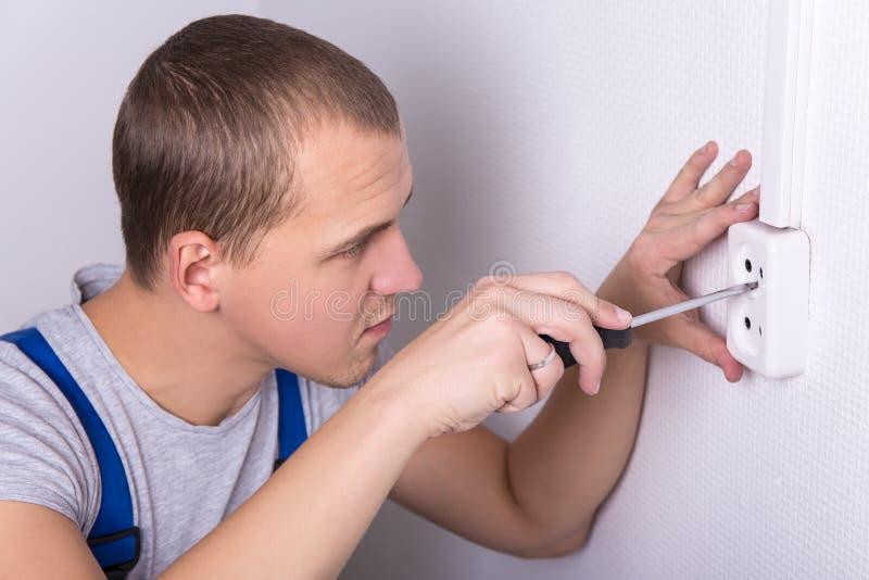 Jonge elektricien die elektrocontactdoos installeren op muur stock fotografie