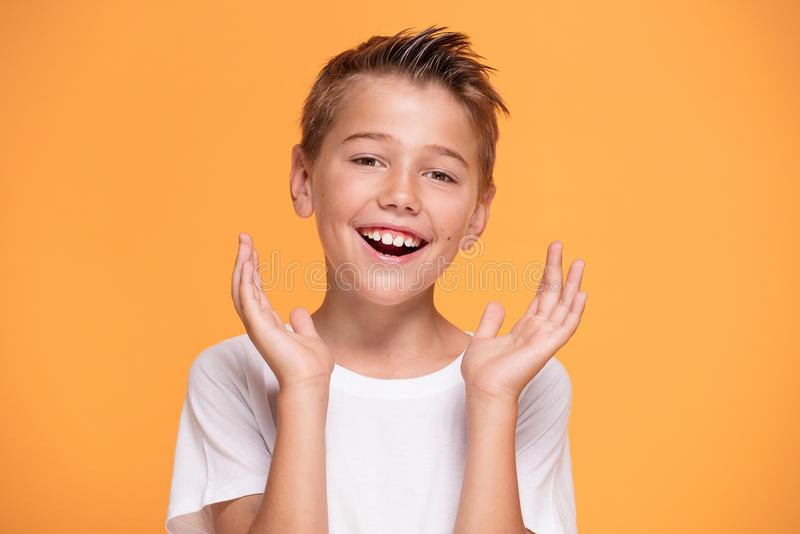 Jonge emotioneel weinig jongen op oranje studioachtergrond stock fotografie
