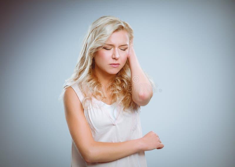 Jonge emotionele die vrouw, op grijze achtergrond wordt geïsoleerd stock foto
