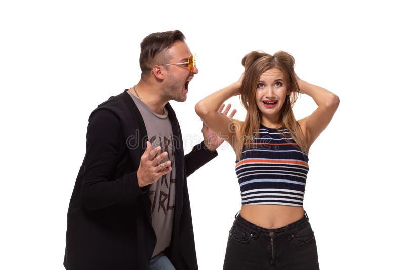 Jonge emotionele man en vrouwenruzie De man die bij de vrouw gillen die haar wapens golven, het meisje behandelde haar oren royalty-vrije stock afbeelding