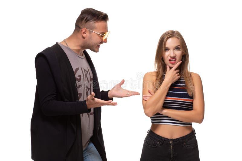 Jonge emotionele man en vrouwenruzie Man die bij de vrouw gillen die haar wapens golven stock afbeelding