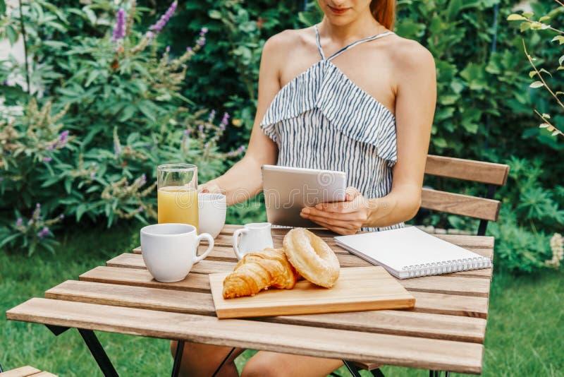 Jonge en Aantrekkelijke Vrouw die Ochtendontbijt in Groene Tuin hebben stock foto