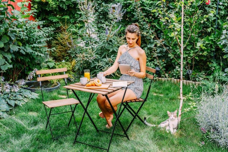 Jonge en Aantrekkelijke Vrouw die Ochtendontbijt in Groene Tuin hebben royalty-vrije stock foto