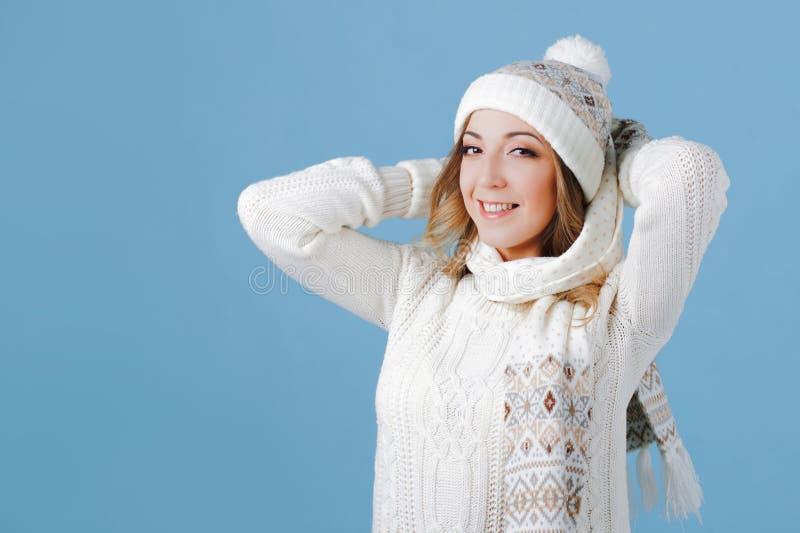 Jonge en aantrekkelijke vrouw in een gebreide sweater, sjaal, hoed, blauwe achtergrond royalty-vrije stock afbeeldingen