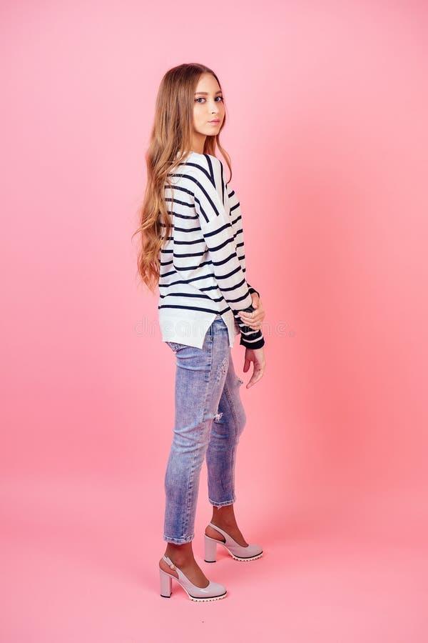 Jonge en aantrekkelijke vrouw, stijlvol model in jeans, schoenen met hoge hak en een sweater in studio op een roze stock afbeelding