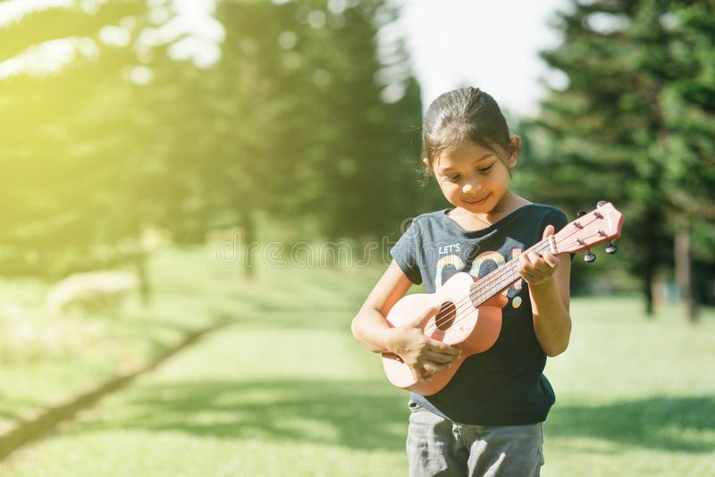 Jonge en gelukkige Aziatische meisje het spelen ukelele gitaar in het park bij zonnige ochtend royalty-vrije stock afbeelding
