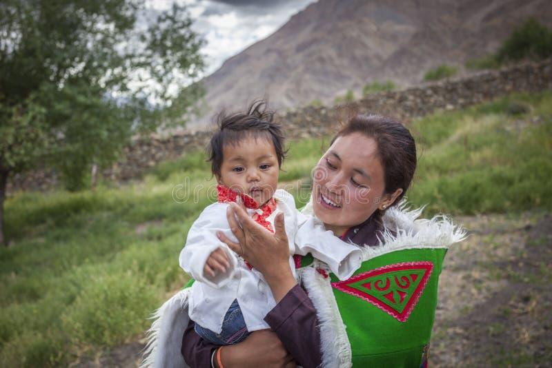 Jonge en gelukkige vrouw die haar leuke baby houden stock afbeelding