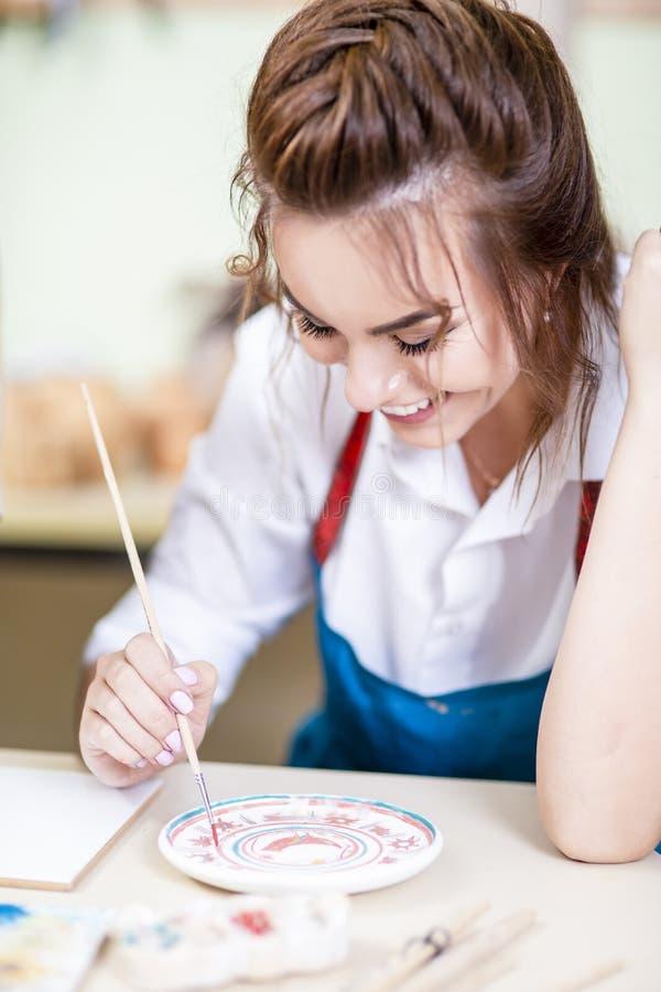 Jonge en Gelukkige Vrouwelijke Ceramist die Penseel voor Verglazing gebruiken royalty-vrije stock foto