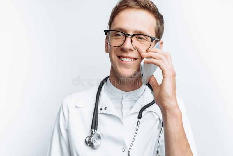 Jonge en knappe arts die op de telefoon met patiënten, Internstudent met in hand omslag, witte achtergrond, voor advertisin sprek royalty-vrije stock afbeelding