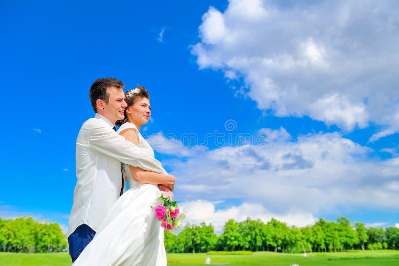 Jonge en knappe jonggehuwden op een gang in het park: bruidegomomhelzingen t stock afbeelding