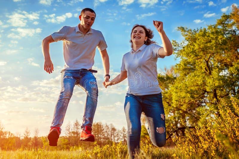 Jonge en man en vrouw die lopen springen Paar die pret op de lentegebied hebben bij zonsondergang Kerels het lachen stock foto's