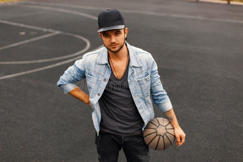 Jonge en modieuze Hipster-mens in een jeansjasje met een bal stock foto's